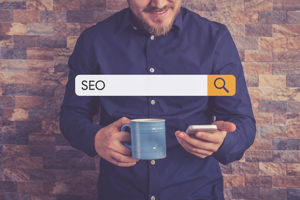 A create professional holding a cup of coffee, surfing on his phone and standing against a brick wall. A search engine screen saying SEO is over his body.