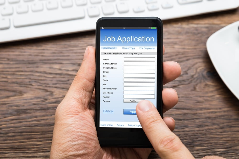 A man fills out a job application on a smartphone
